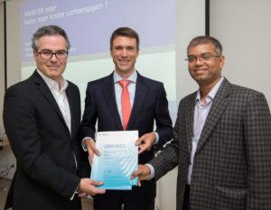 S. Müller (mitte) übergibt den Forschungsbescheid an Prof. Dr. J. Vera-González der Dermatologischen Klinik (links) und Dr. S. Gupta von der Universität Rostock. (Foto: FAU/Erich Malter)
